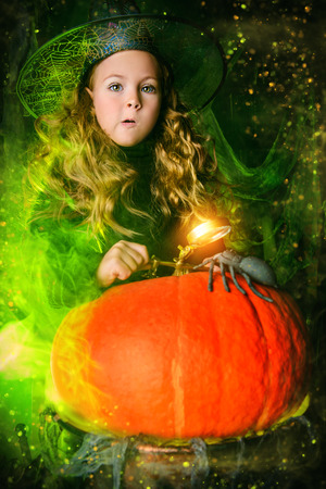Happy Halloween. Cute surprised child girl in witch costume is in a witch's lair with pumpkin. Standard-Bild - 108314576