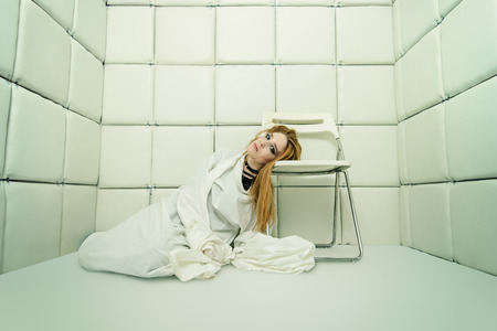 Portrait of a crazy girl dressed in a straitjacket in an isolated room in a madhouse.