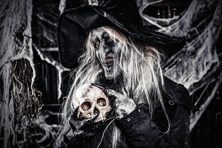 A witch holding a skull. Halloween. Horror movie. 写真素材