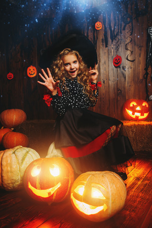 Cute curly girl in a costume of a witch holds pumpkin-lantern. Halloween party.