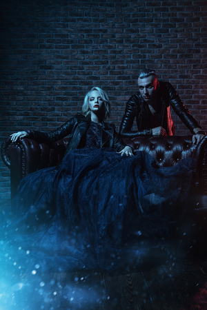 A beautiful couple of vampires in a dark room. Beauty, fashion.