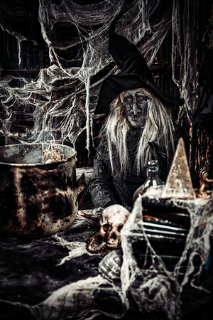 A scary witch is sitting at a lair. Halloween. Horror movie.