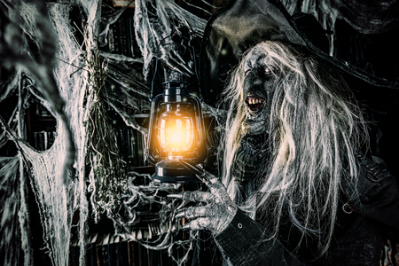 A witch holding a torch. Halloween. Horror movie.