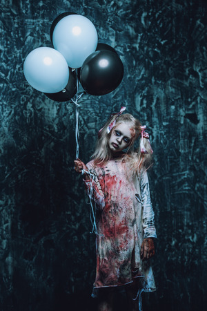 A portrait of a scary girl holding balloons. Halloween. Horror film.