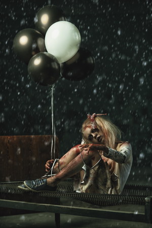 A scary girl sitting on a bed with balloons. Halloween. Horror film.