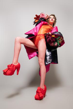 Coup de Vogue d'un modèle féminin posant au studio. Collection de mode. Portrait en pied sur fond blanc. Banque d'images - 108677052