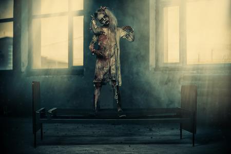 Un retrato de cuerpo entero de una niña aterradora de pie sobre una cama. Víspera de Todos los Santos. Película de terror.