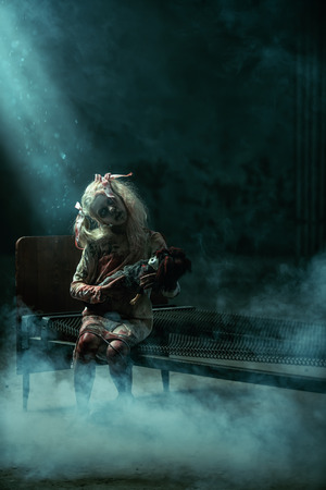 A scary girl sitting on a bed with a toy. Halloween. Horror film.