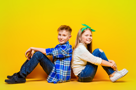 Childrens fashion. Beautiful  little children sitting at studio over yellow background. Laughing and happy.