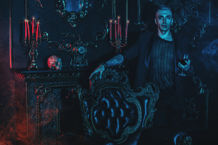 A vampire man is standing in a dark room and drinking wine or blood. Halloween. Beauty, fashion, horror.