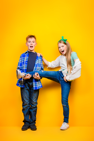 Full length portrait of happy boy and girl over bright yellow background. Kids fashion.