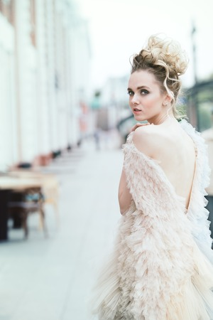 Beautiful young woman is walking around the city in an elegant fluffy dress. Beauty, street fashion.