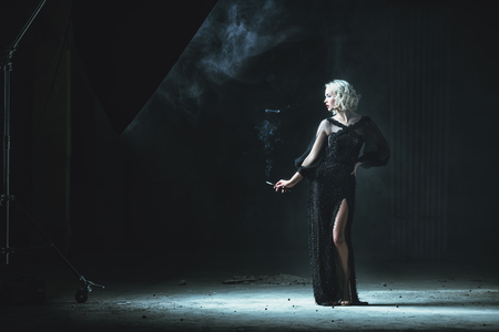 A full length portrait of a beautiful blonde lady smoking a cigarette. Evening dress. Fashion, beauty.