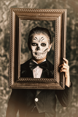 Portrait of a child boy with carnival make-up of a skeleton wearing elegant tail-coat. Studio shot over dark grunge background. Halloween.  The Day of the Dead.
