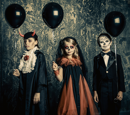 Three children in halloween carnival costumes stand by a grunge wall with black balloons. Happy Halloween! Stock fotó