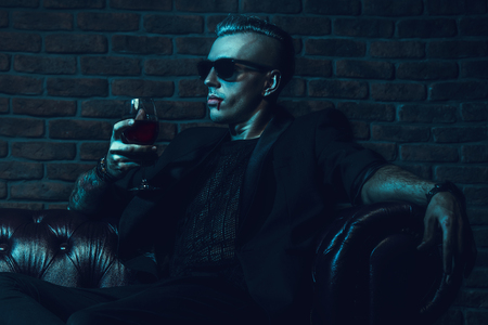 A vampire man in glasses is sitting in a dark room and drinking wine. Classic style. Beauty, fashion. Stock Photo