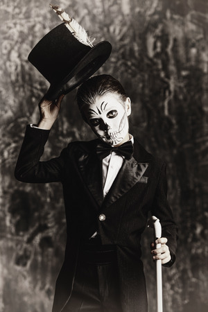 Portrait of a child boy with carnival make-up of a skeleton wearing elegant tail-coat. Studio shot over dark grunge background. Halloween. The Day of the Dead. Stock fotó