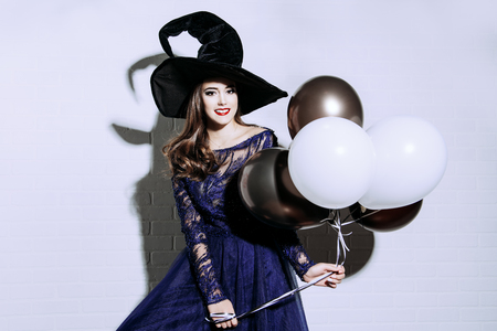 A beautiful lady in a costume of witch. Halloween. Celebration. Imagens - 108959617