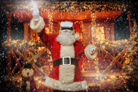 Santa Claus in virtual reality glasses is standing in the yard. Christmas and New Year time.