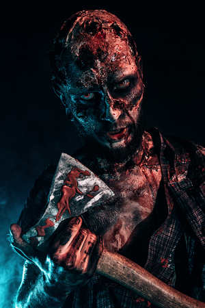 Portrait of a scary zombie with an axe. Halloween. Horror film. Banque d'images