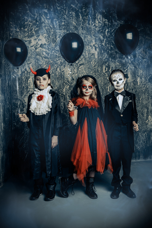 Three children in halloween carnival costumes stand by a grunge wall with black balloons. Happy Halloween! Фото со стока
