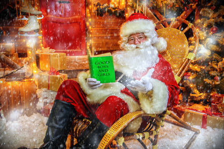 Santa Claus is preparing for Christmas, he reads a book with children's desires. House of Santa Claus. Christmas decoration.