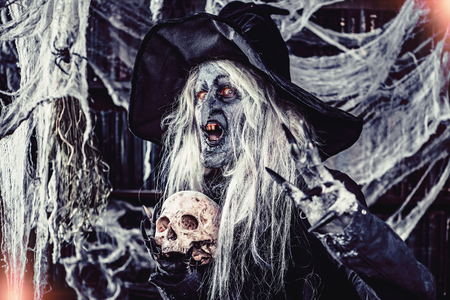 A witch holding a skull. Halloween. Horror movie. Stock Photo