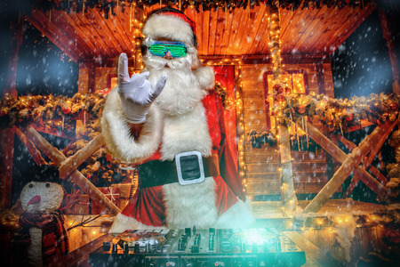 DJ Santa Claus in luminous glasses and headphones holds a party near his house decorated with lights. Christmas songs and music.