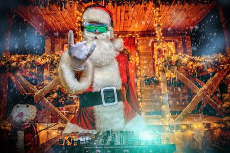 DJ Santa Claus in lichtgevende glazen en koptelefoons houdt een feest in de buurt van zijn huis versierd met verlichting. Kerstliedjes en muziek. Stockfoto