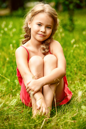 A cute little girl is sitting on the grass in the countryside. Fashion, beauty. Summer.