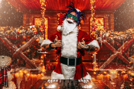 Ð¡razy punk Santa Claus in luminous glasses and headphones holds a party near his house decorated with lights. Christmas cool party. Stock fotó