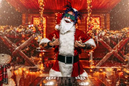 Ra¡razy Punk Weihnachtsmann in leuchtenden Gläsern und Kopfhörern veranstaltet eine Party in der Nähe seines Hauses mit Lichtern geschmückt. Coole Weihnachtsfeier. Standard-Bild
