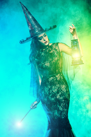 A beautiful lady in a costume of witch holding a torch. Halloween. Celebration. Stock Photo