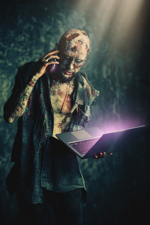 Creepy scary zombie is talking on the phone with a laptop. Halloween. Horror film.
