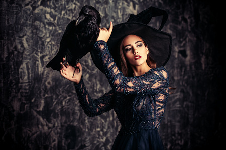 A witch in hat and dress with a raven. Halloween. Celebration. Stok Fotoğraf - 109269925