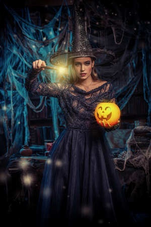 A witch in a castle holding a lantern and a pumpkin. Halloween. Celebration.
