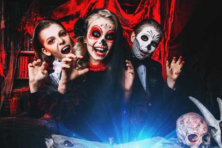 Halloween party. Cheerful children in carnival costumes celebrate halloween in the scenery of the witch's lair. Standard-Bild - 109270014