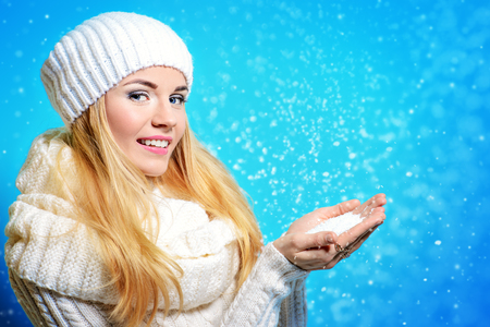 Winter beauty, cosmetics. Beautiful blonde girl wearing white woolen clothes holding snow in her palms and smiling. Winter fashion concept.