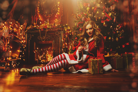 Beautiful girl in red Santa suit sits on the floor near the fireplace and Christmas tree with a gift box. Magical Christmas night in luxurious apartments decorated Christmas lights.