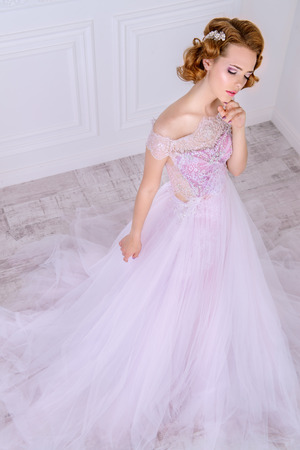 Charming bride woman in a beautiful wedding dress  with a lush skirt. Luxurious apartments. 스톡 콘텐츠