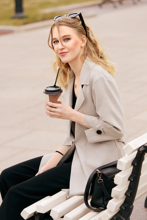 Beautiful young woman in a leather jacket is sitting on the street. Spring and autumn fashion.