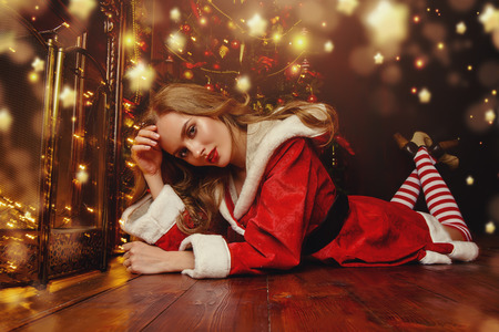 Beautiful girl in red Santa suit lies on the floor near the fireplace and Christmas tree. Magical Christmas night in luxurious apartments decorated Christmas lights.