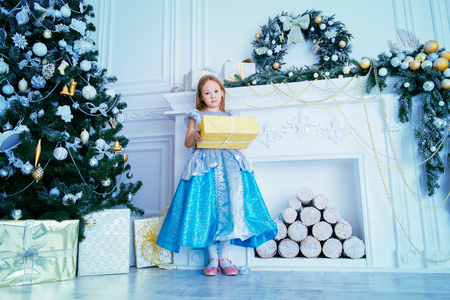 Cute six year old girl stands near the Christmas tree in a elegant dress with a gift box. Christmas, fashion concept. Classic luxurious interior decorated for Christmas. Stock Photo