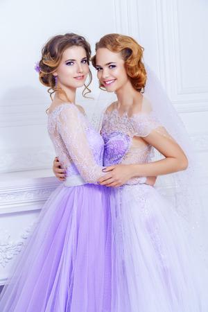 Charmante Braut und Brautjungfer stehen zusammen in schönen Kleidern und lächeln. Hochzeitsmode.
