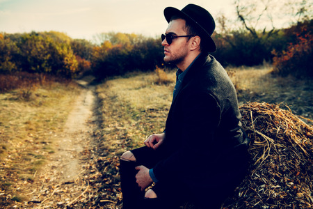 Seasonal autumn fashion. Portrait of a handsome man wearing black coat, a hat and sunglasses. Autumn nature. Stok Fotoğraf - 109773135