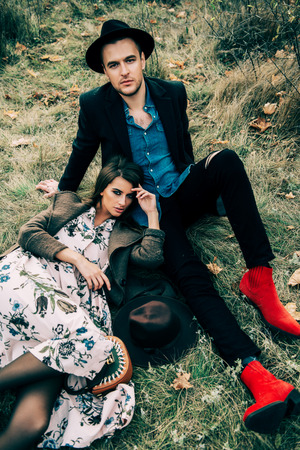 Autumn fashion. Beautiful fashionable couple lying on yellowed autumn grass and leaves.