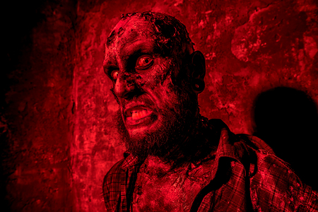 Creepy scary zombie in red light. Halloween. Horror film. Stock Photo