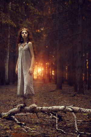 Geheimnisvolles schönes Mädchen, das in einem dunklen Wald aufwirft. Schönheit, Mode im Freien. Standard-Bild