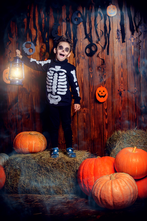 Halloween party. Funny little boy in a skeleton costume  with big pumpkins.
