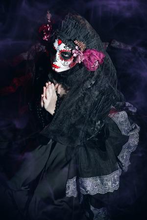 Calavera Catrina in darkness. Sugar skull makeup. Dia de los muertos. Day of The Dead. Halloween. Фото со стока